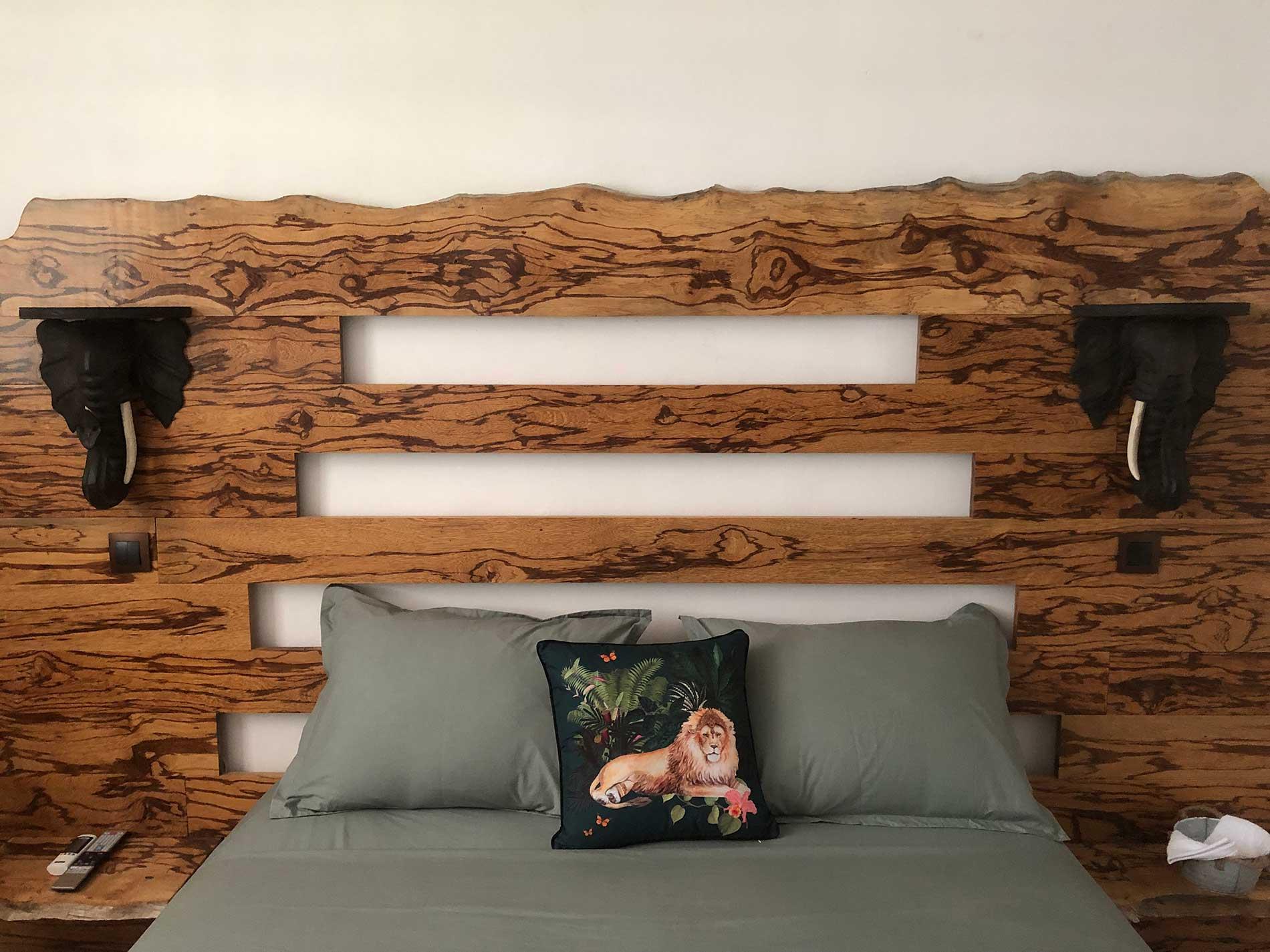 Tête de lit faite sur mesure en bois serpent avec ses deux appliques en éléphant. L