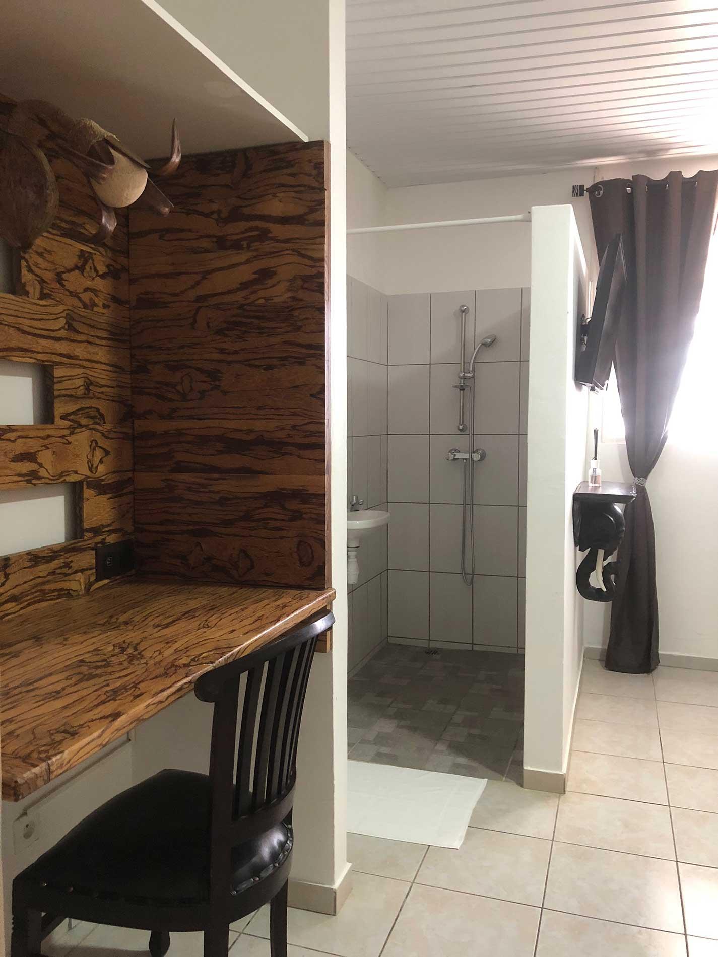 La salle de bain est ouverte sur la chambre. Elle peut être fermée par un rideau. Il y a un lavabo et une colonne de douche avec un mitigeur thermostatique.la