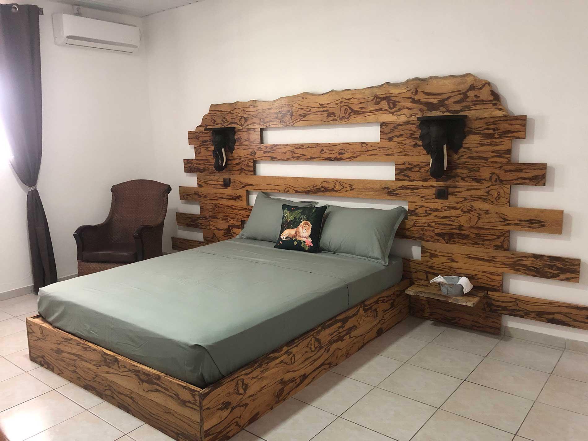 Le lit en bois serpent comprend deux appliques en ébène en forme d'éléphant, deux tablettes et un éclairage indirect très confortable.