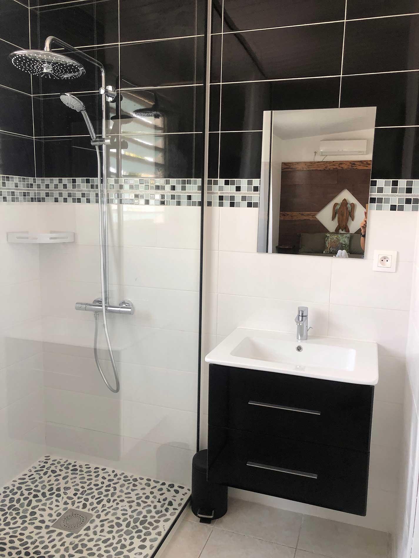 A l'autre extrémité de la chambre, on retrouve la salle de bain à dominante noir et blanc. Salle de bain avec une douche à l'italienne et un lavabo.