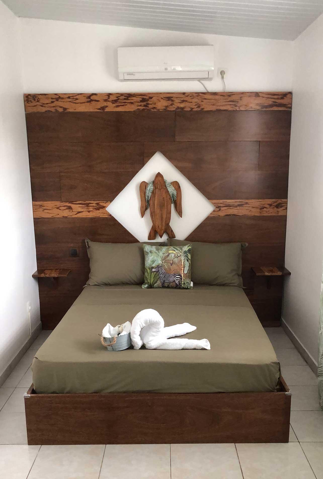 Vu sur le lit en bois coeur dehors et bois serpent. Au centre dans un losange de lumière, on trouve une tortue de 80cm de diamètre toute en bois serpent. La tête de lit comprend deux tablettes pour poser les affaires personnelles (télécommandes, téléphones, tablettes...)