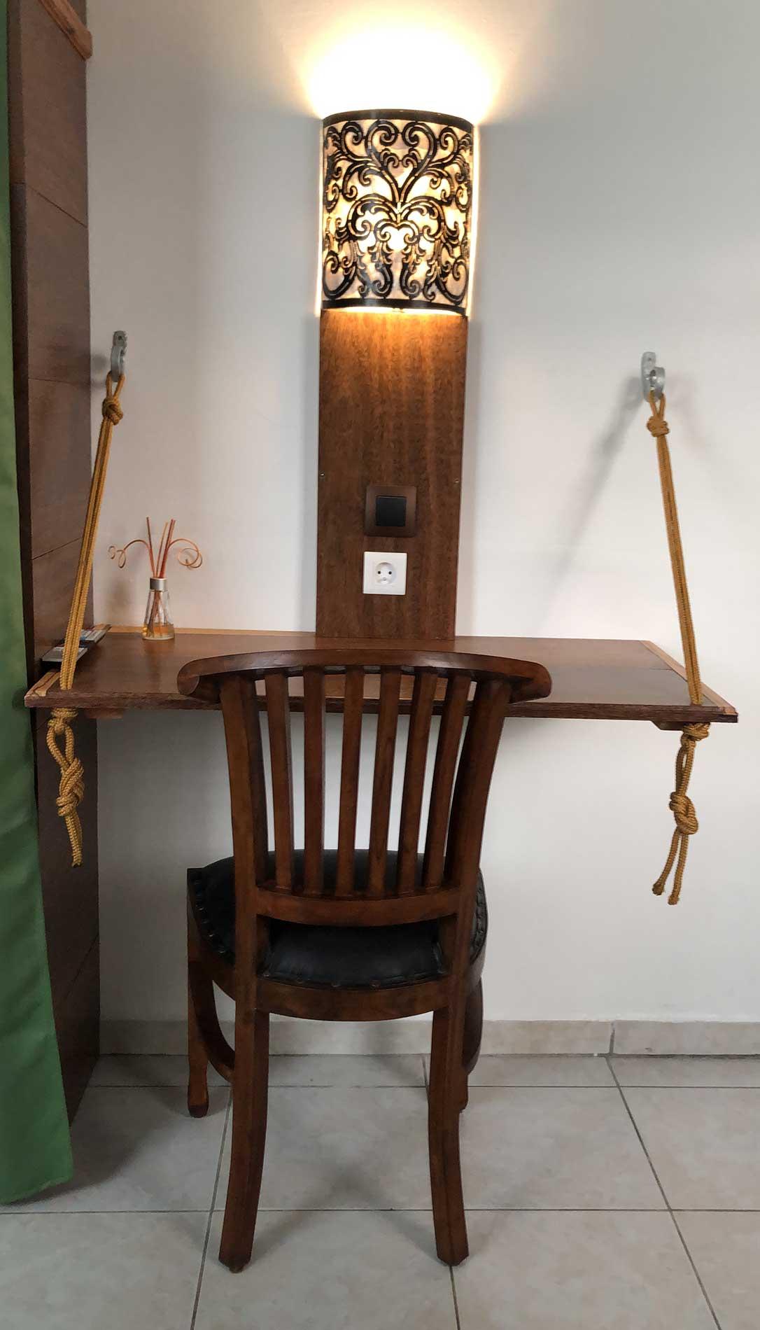 Vue sur le bureau en coeur dehors et en bois serpent. Le bureau est suspendu par des cordes au mur. Au centre du bureau on trouve la lumière indirect en nacre et fer forgé noir.