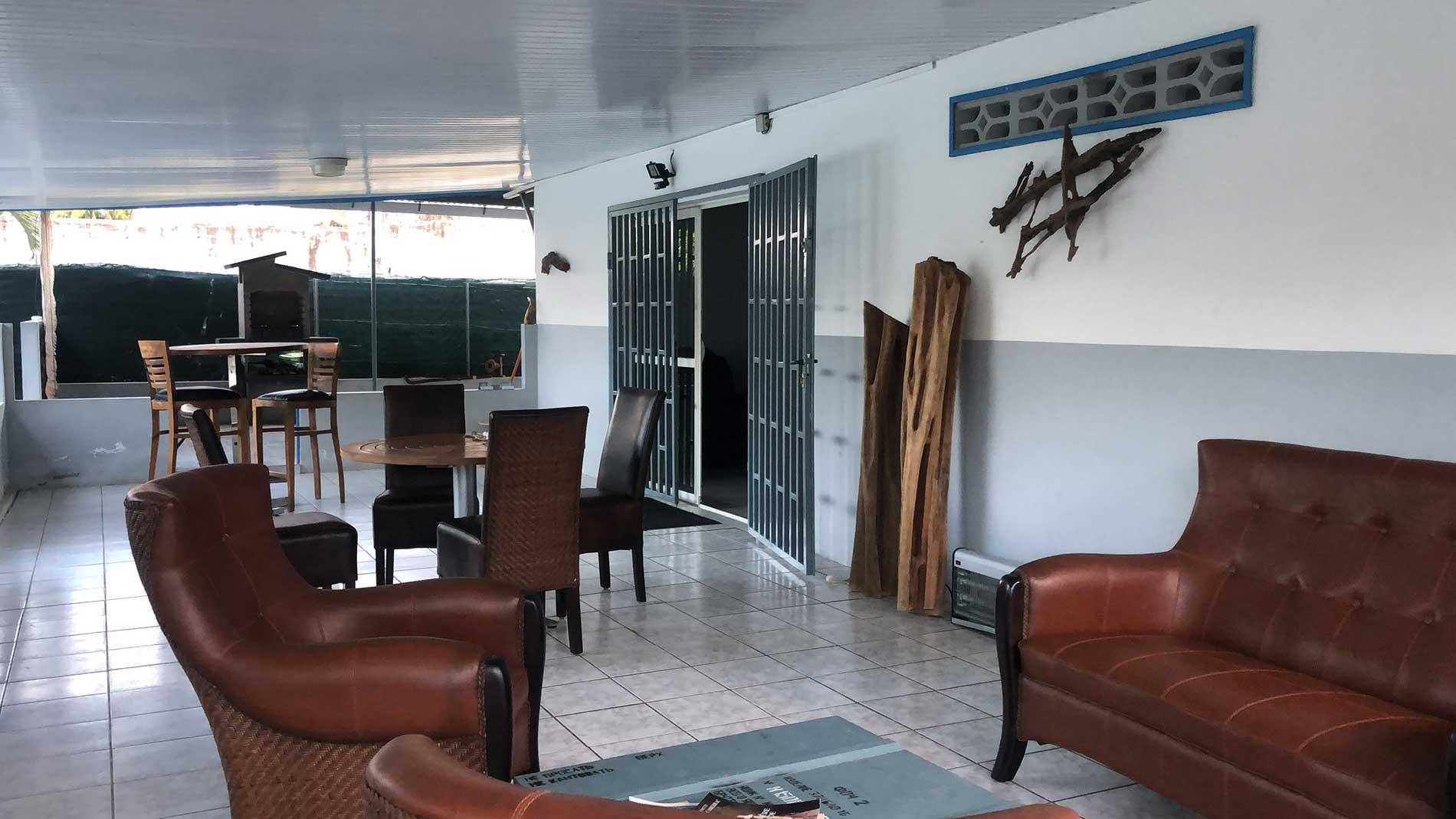Vue générale de la terrasse avec son espace détente (deux fauteuils et un canapé), sa table pour quatre personnes en teck et sa table haute pour deux personnes. En fond on distingue le barbecue commun.