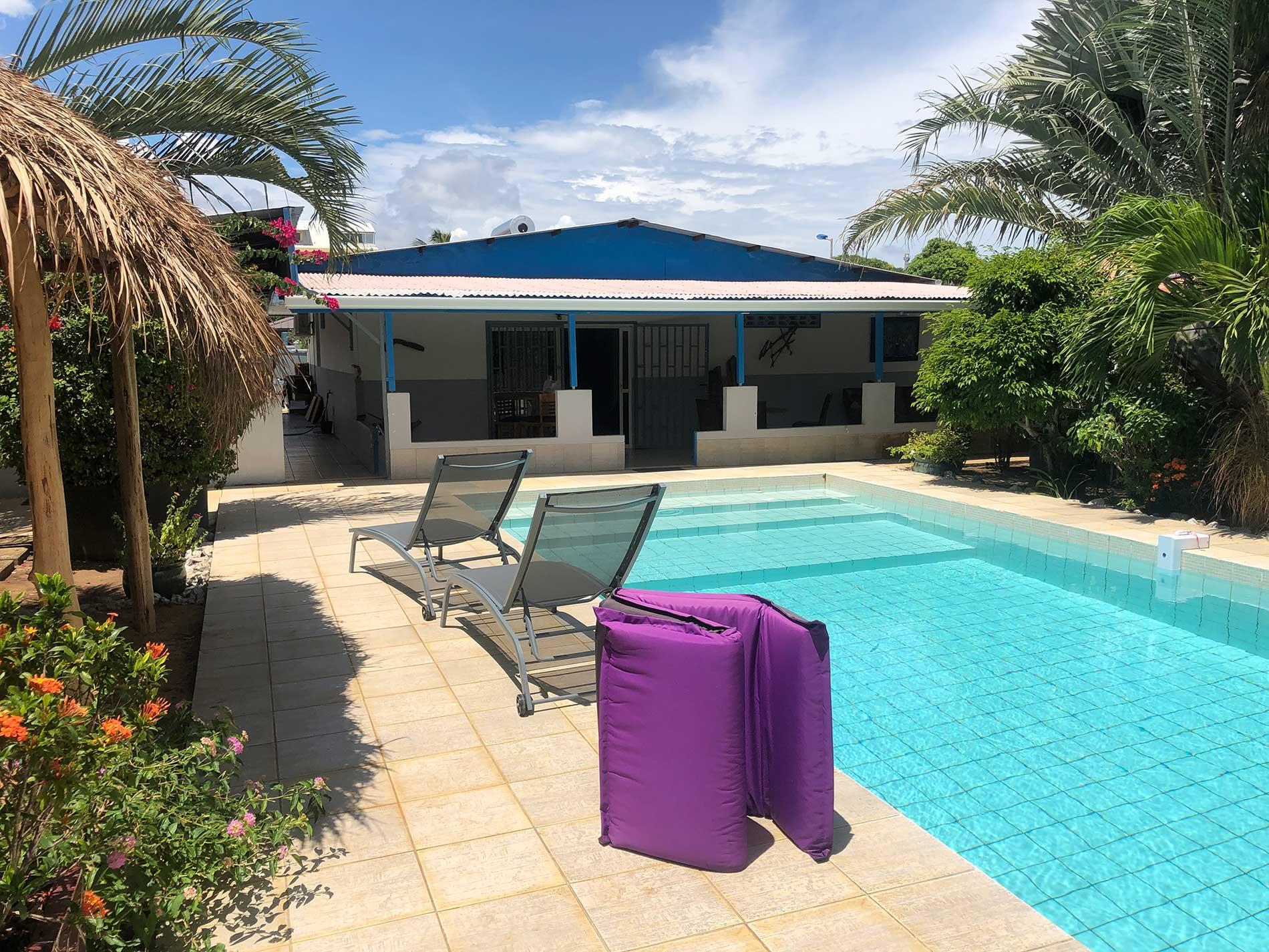 Vue de la piscine depuis les studios toucan et toco. Eau bleue, ciel bleu, bain de soleil avec végétation tropicale
