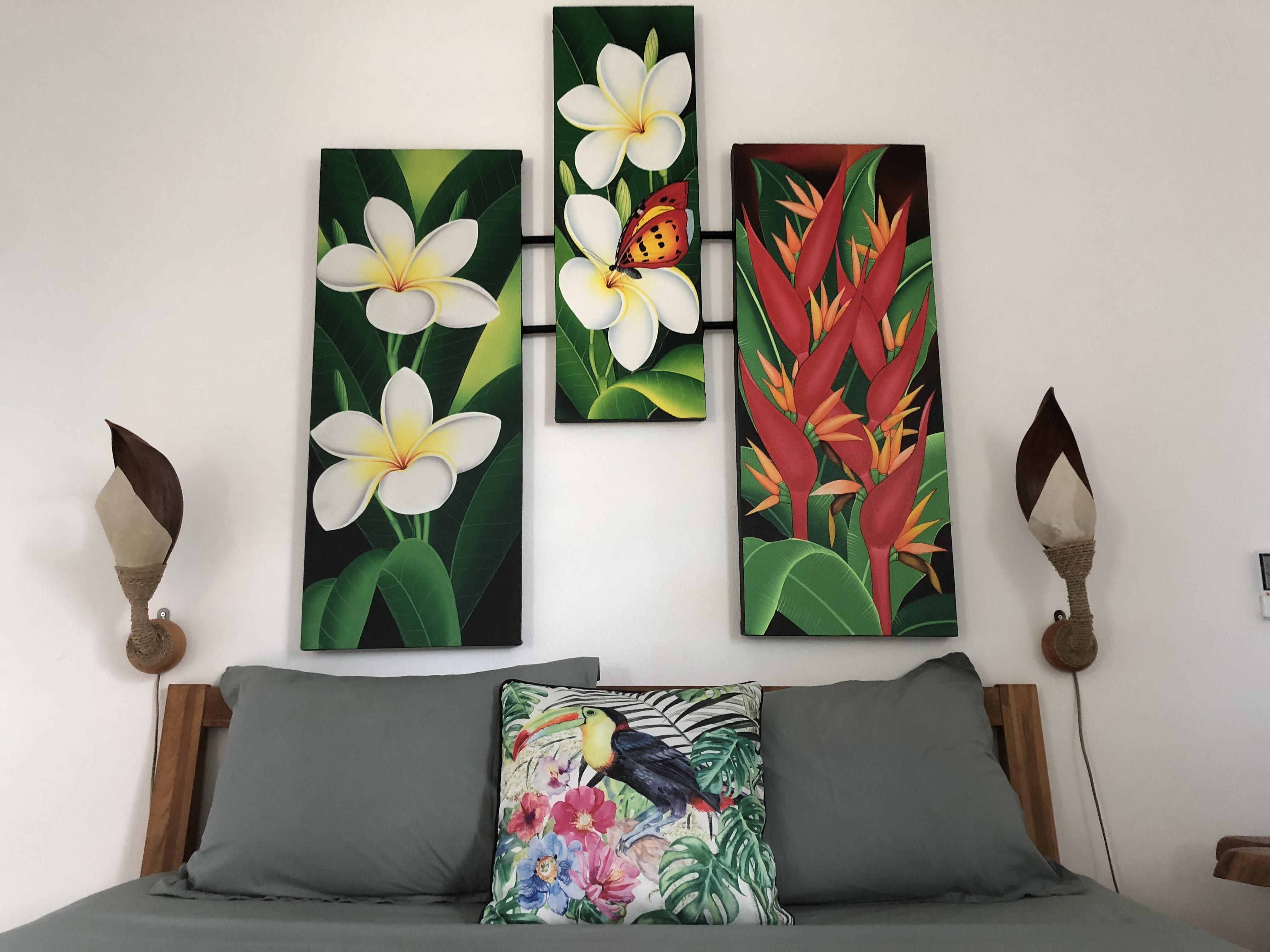 Vue de face sur la tête de lit fleurie et colorée, les applique murale et les coussins modulables