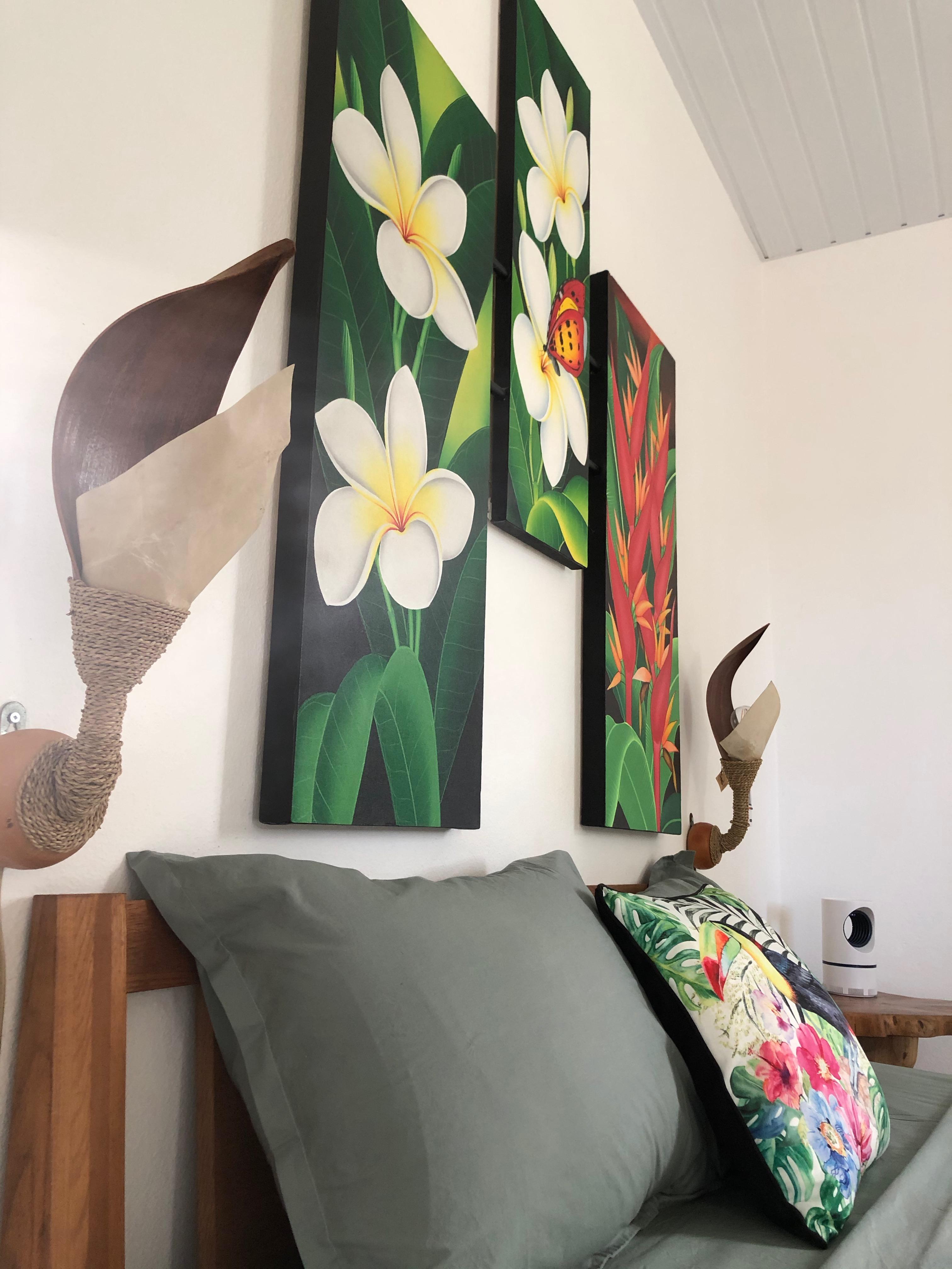 Zoom sur le triptyque de la tête de lit fleuri et coloré avec les 2 appliques murales en coque en maripa
