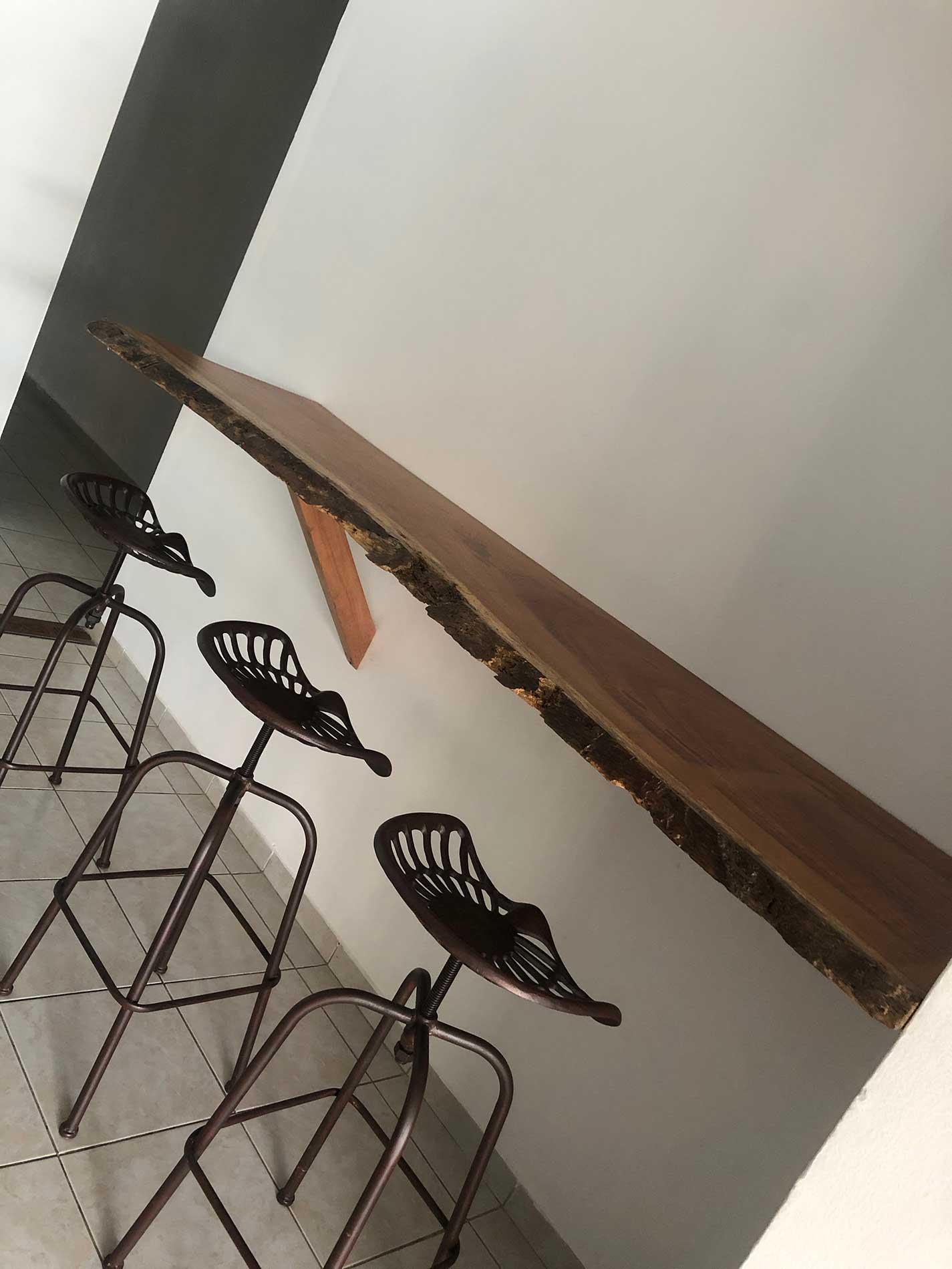 Vue sur la table haute qui a été créee en bois Saint Martin jaune et ses trois chaises hautes en fonte
