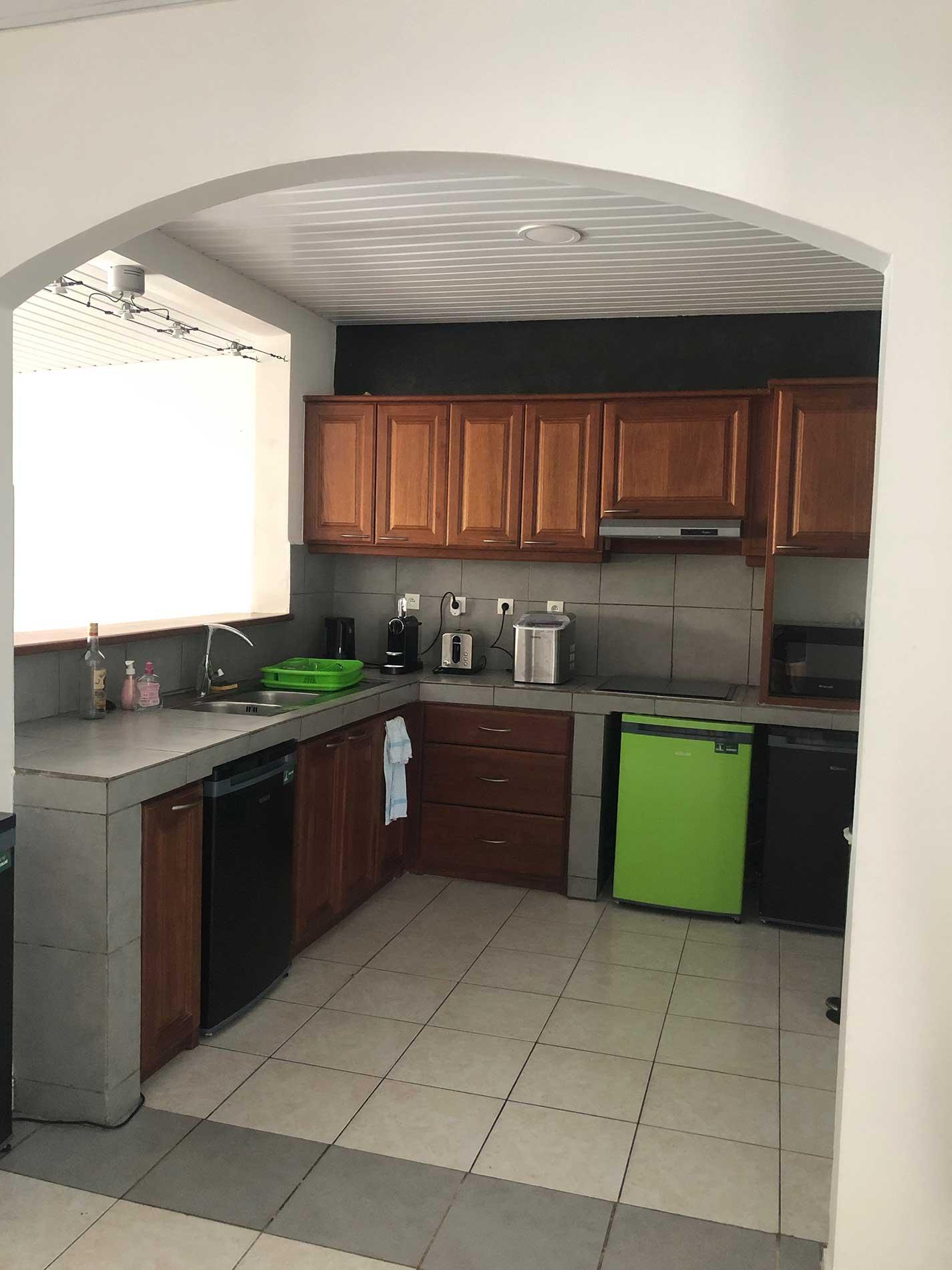 Photo de la cuisine où l'on voit les quatre frigos individuels, les nombreux placards, l'évier, le très grand plan de travail, la machine à glaçons, la nespresso, la bouilloire...