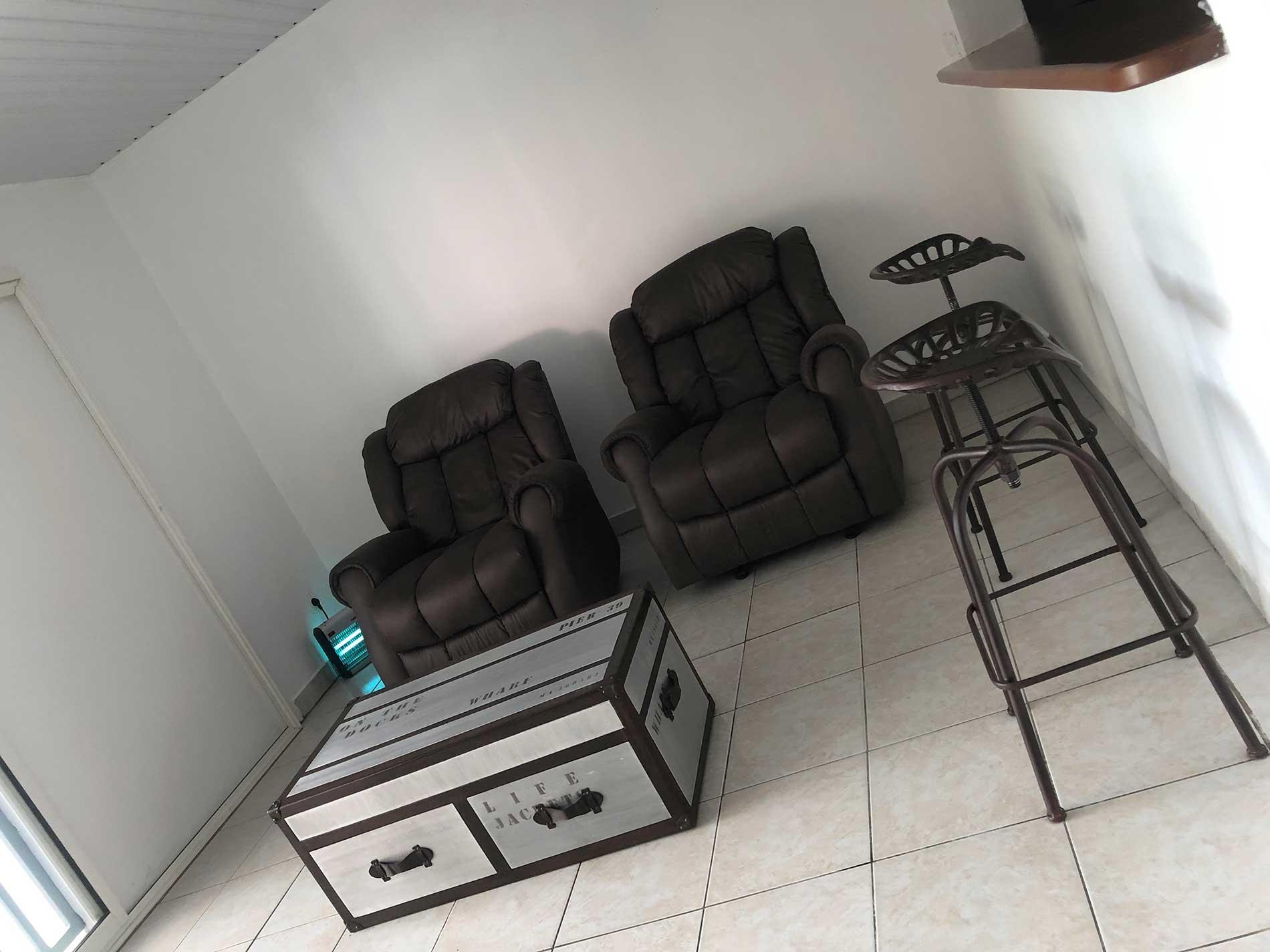 Photo de l'espace détente avec sa table basse en coffre fort, et les deux des quatre fauteuils relaxants