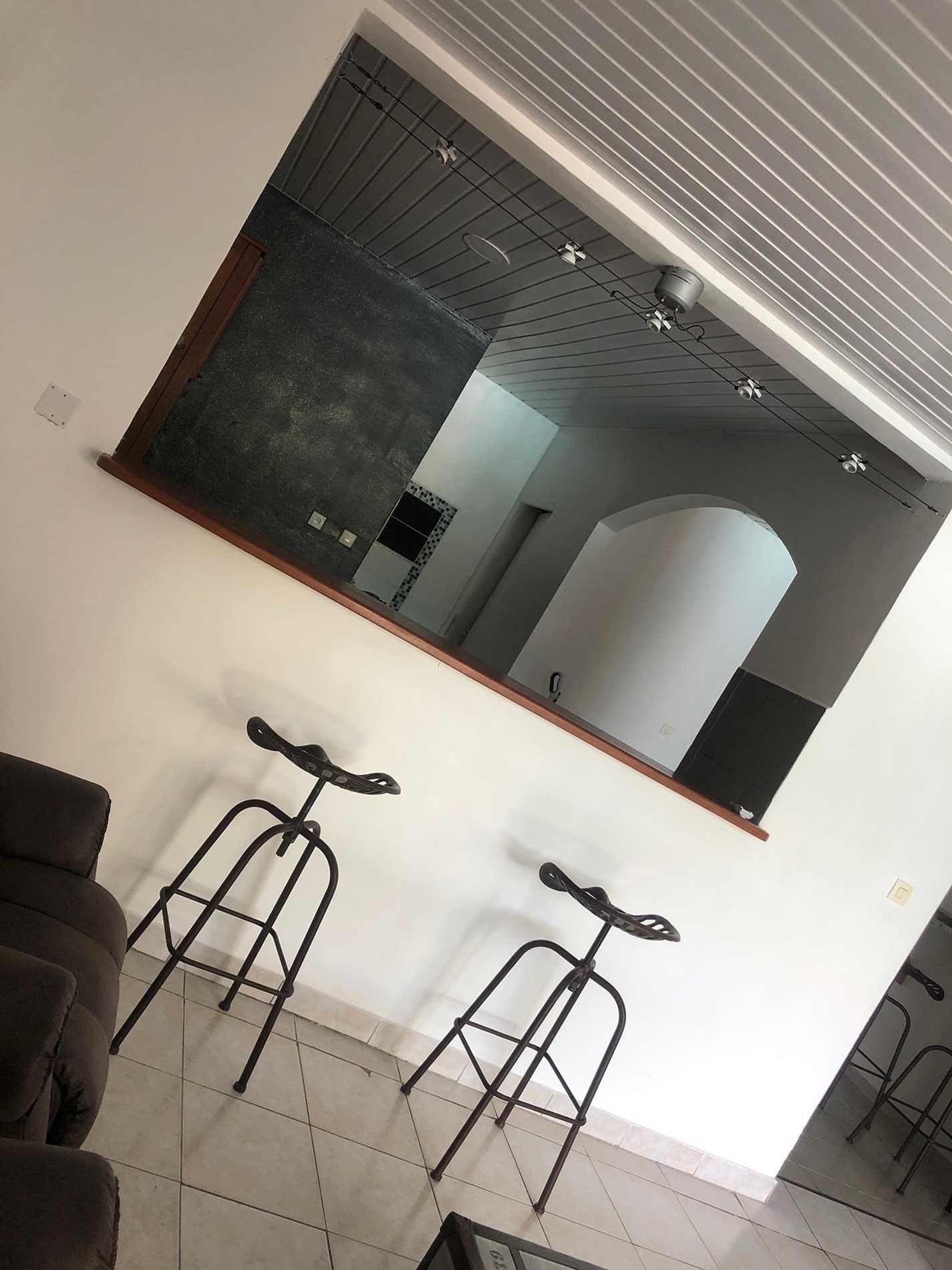 Vue sur l'espace repas qui sépare l'espace détente de le cuisine avec ses deux chaises hautes en fote