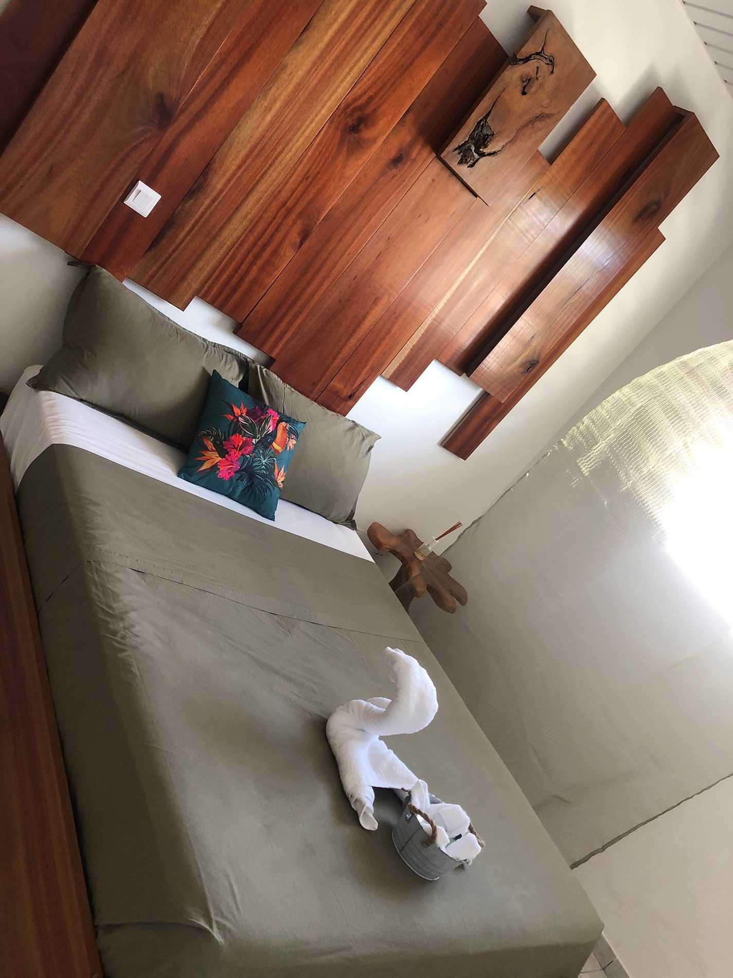 Tête de lit artisanale faite en bois coeur dehors avec un éclairage indirect accessible depuis le lit. Le lit 140x190 et ses coussins modulables.