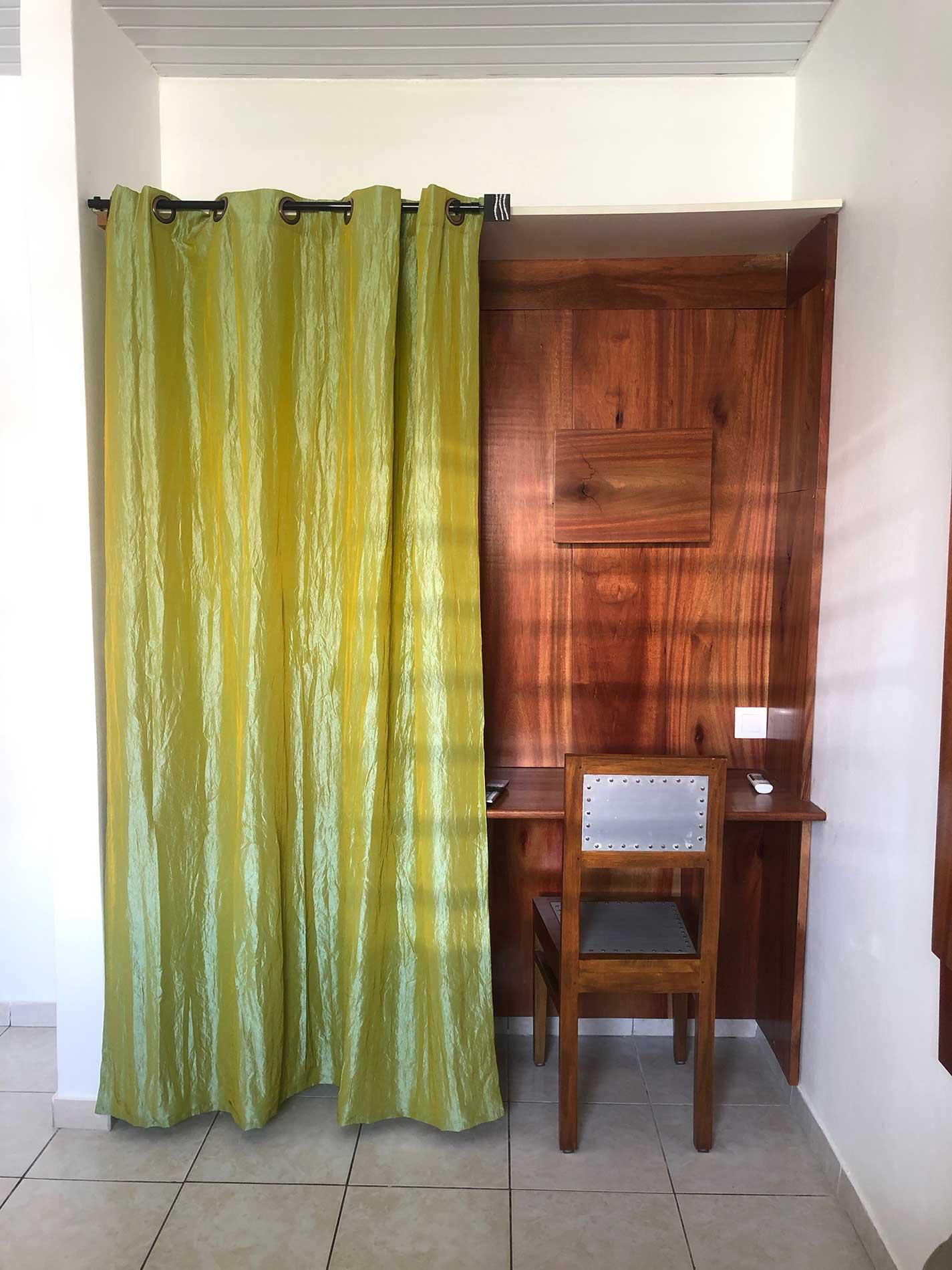 Bureau fait en bois satiné rubané en harmonie avec le lit. Sa chaise en bois et métal. A côté la penderie pour ranger les affaires.