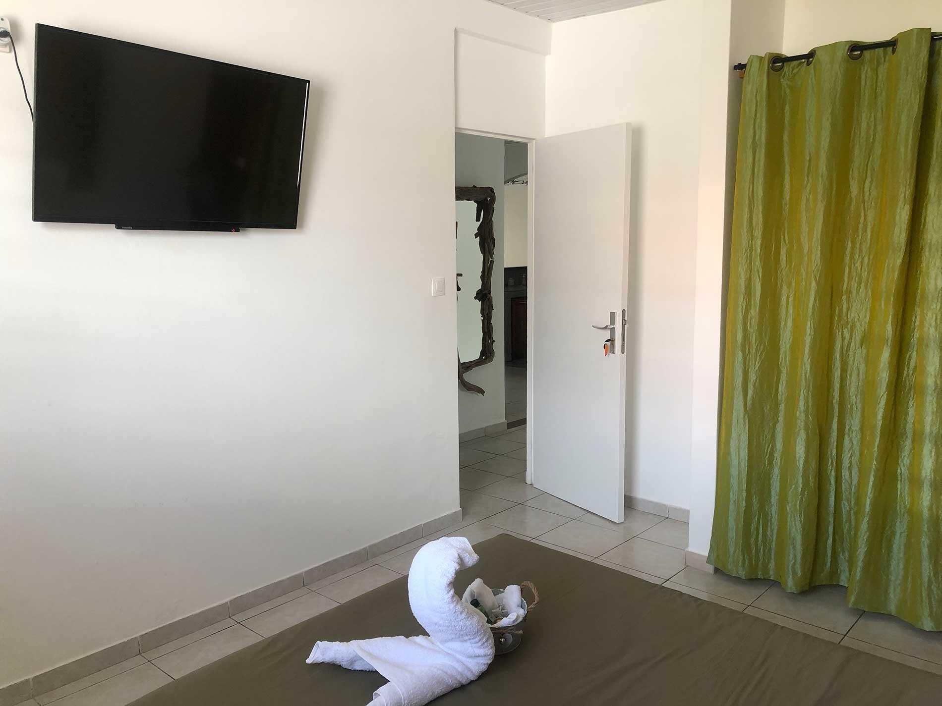 Vue depuis le lit sur la télévision (TV) connectée, la penderie et la porte d'entrée de la chambre.