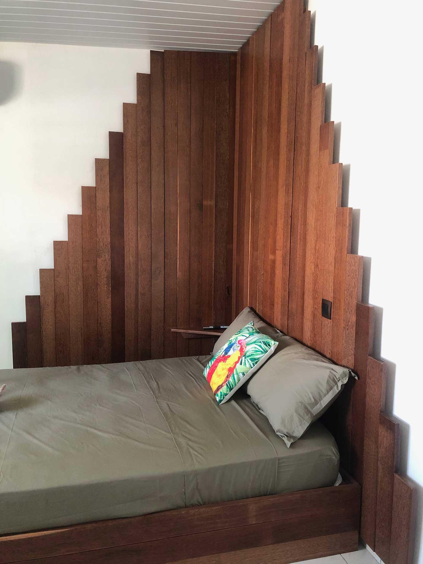 Vue sur la tête de lit en forme de pyramise faite en bois wacapou