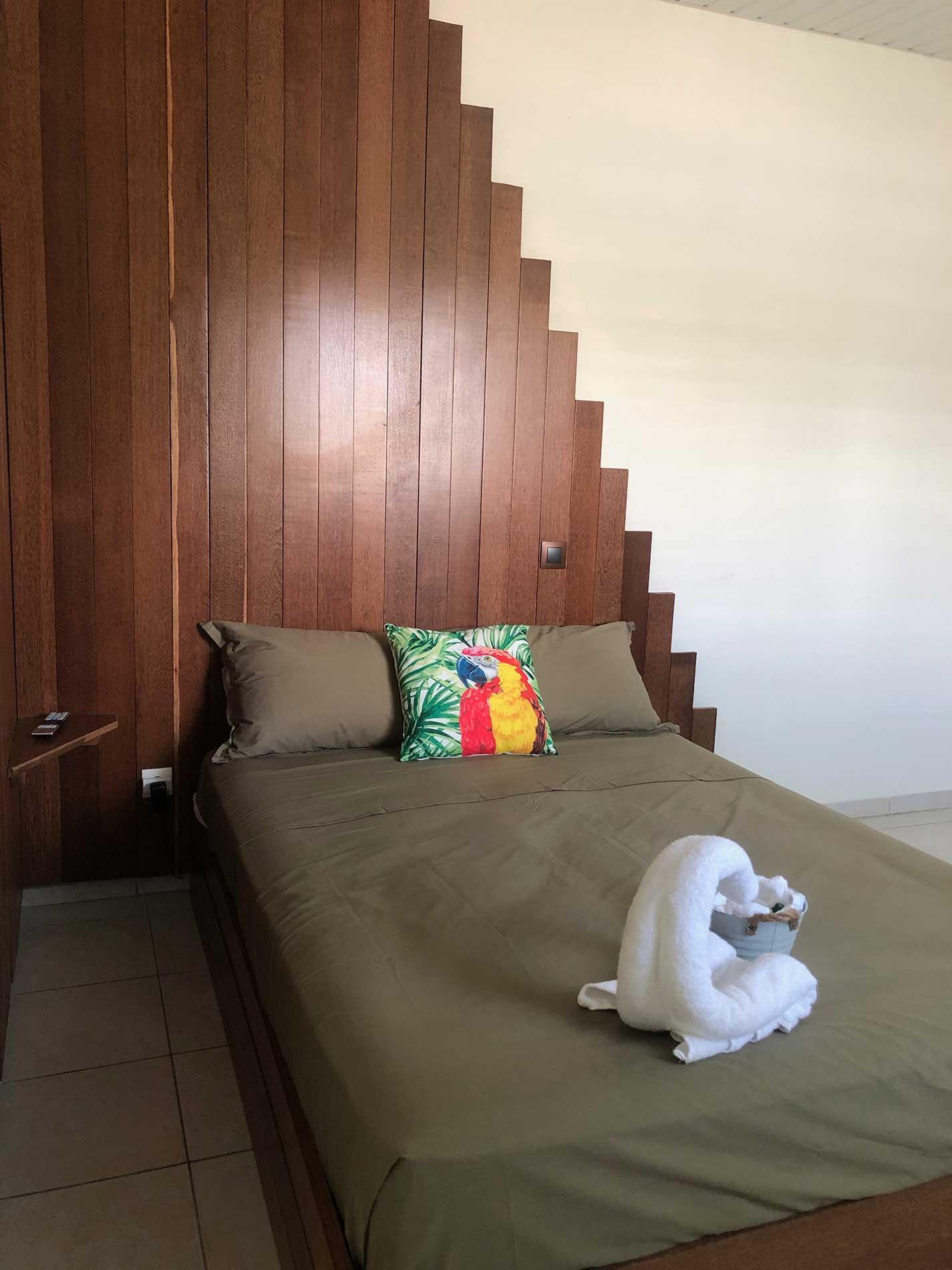 Vu rapprochée du lit en bois Wacapou. La tête de lit est en forme de pyramide avec une tablette pour poser ses affaires personnelles et un interrupteur pour commander l'éclairage direct de la tête de lit.