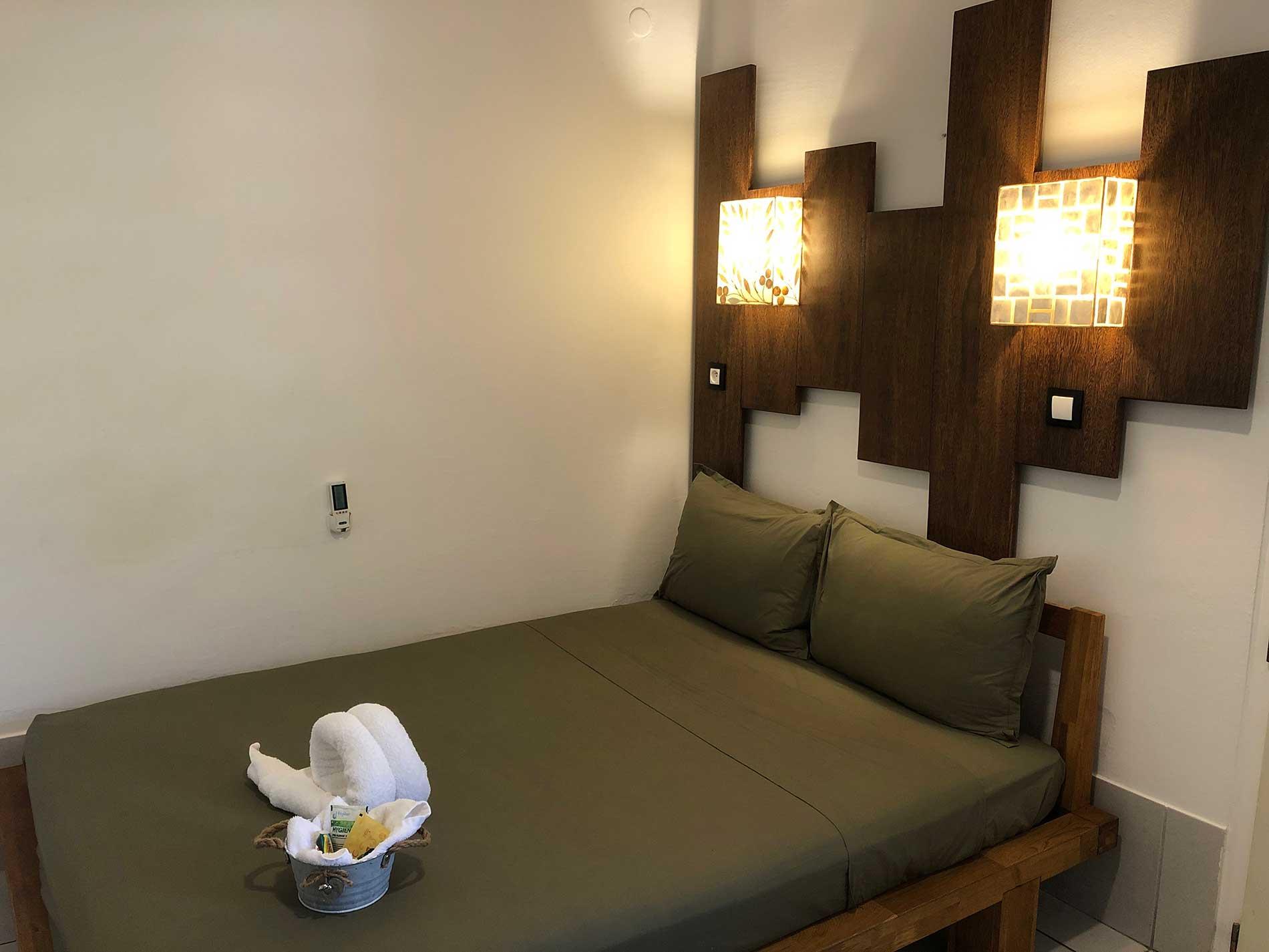 Vue sur le lit en bois local, la literie pro et les coussins modulables